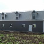 Metal roofing and siding on hip roof building